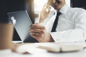 Australischer Investor sitzt am Schreibtisch, telefoniert und liest auf Tablet