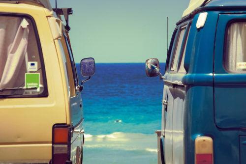 Zwei Campingbusse vor australischem Strand