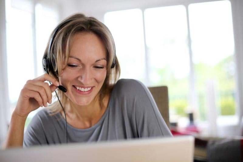 Frau sitzt vor einem Computer und Erhalt eine Visumsberatung über Skype