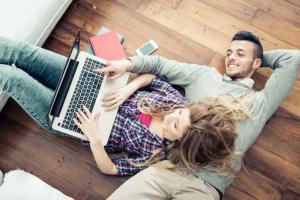 Auf dem Boden liegendes Paar füllt den Fragebogen für einen Visums Kurzcheck aus