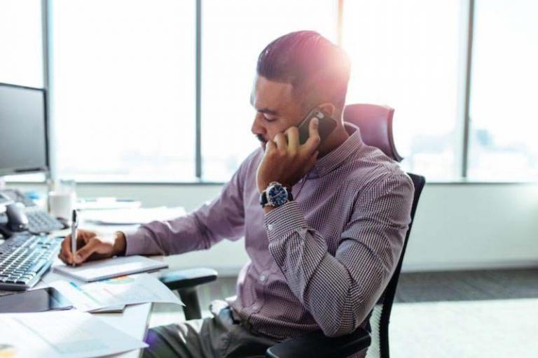 Australischer Unternehmer sitzt an seinem Schreibtisch und telefoniert