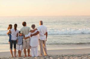 Drei Generationen einer australischen Familie stehen am Strand