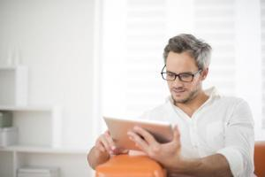 Mann sitzt auf der Couch und liest auf einem Tabletcomputer ein Visumsgutachten