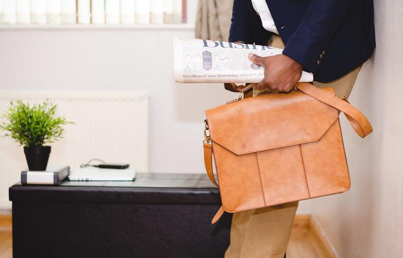 Geschäftsmann mit australischem Businessvisum hält Tasche und Zeitung
