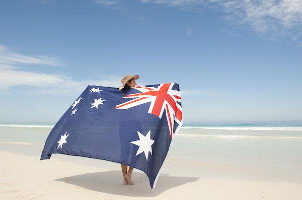 Frau steht mit australischer Flagge am Strand