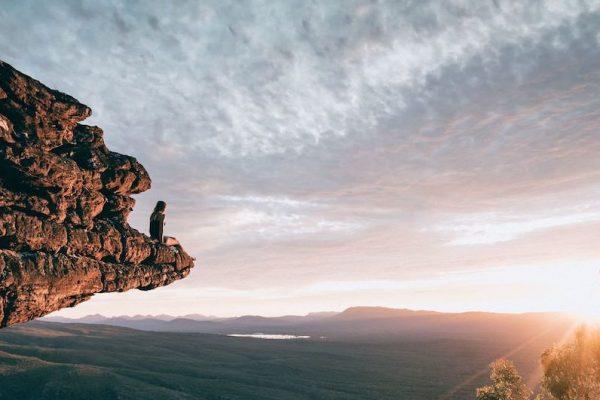 Work and Travel Reisende sitzt auf Felsen und blickt in die Ferne